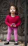 Fussy little girl. 2 year old girl posing with a cell phone royalty free stock images