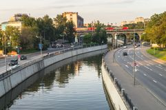 View of the railway bridge over the Yauza river and roadway of its embankment in sunset light, Moscow. In the fussy noisy Moscow sometimes you want to stop and stock image