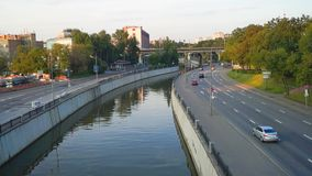 View of the river Yauza and roadway of its embankment in sunset light, Moscow. stock footage