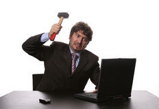 Fustrated businessman. In his office threatening to destroy his PC with a hammer out of sheer frustration Royalty Free Stock Photo