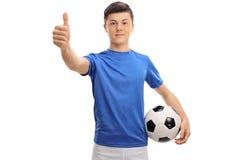 Futbolista adolescente que hace un pulgar encima de la muestra Imagen de archivo