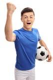 Futbolista adolescente que mira la cámara y que gesticula happine Imagen de archivo libre de regalías