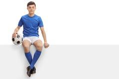 Futbolista adolescente que se sienta en un panel Foto de archivo libre de regalías