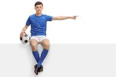 Futbolista adolescente que se sienta en un panel y que señala a la derecha Fotos de archivo libres de regalías