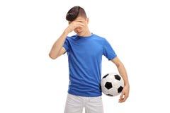 Futbolista adolescente trastornado que celebra su cabeza con incredulidad Imagen de archivo