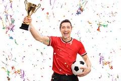 Futbolista alegre que celebra un trofeo imagen de archivo