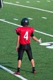 Futbolista americano de la High School secundaria con los pulgares para arriba en el campo Fotos de archivo