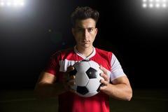 Futbolista apuesto con el balón de fútbol foto de archivo
