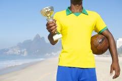 Futbolista brasileño Holding Trophy del campeón y balón de fútbol foto de archivo libre de regalías