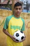 Futbolista brasileño joven que celebra el balón de fútbol Fotos de archivo libres de regalías