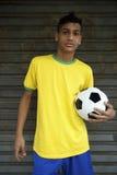 Futbolista brasileño joven que celebra el balón de fútbol Imagen de archivo libre de regalías