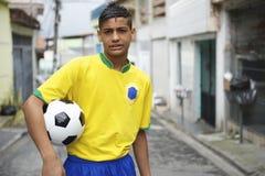 Futbolista brasileño joven que celebra el balón de fútbol en la calle Fotos de archivo libres de regalías