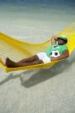 Futbolista brasileño que se relaja en hamaca de la playa fotografía de archivo