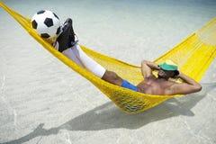 Futbolista brasileño Relaxing con el fútbol Balll en hamaca de la playa fotos de archivo libres de regalías