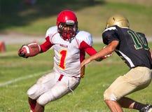 Futbolista de la High School secundaria que corre con la bola Fotografía de archivo libre de regalías