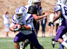 Futbolista de la High School secundaria que corre con la bola durante un juego Foto de archivo libre de regalías