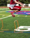 Futbolista de la High School secundaria que limita sobre obstáculos Foto de archivo libre de regalías