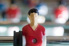 Futbolista en la barra de Foosball Imagenes de archivo