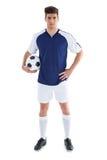 Futbolista en la situación azul con la bola Imagen de archivo