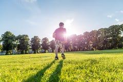 Futbolista joven del muchacho en el estadio que camina hacia el sol Fotos de archivo