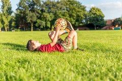 Futbolista joven del muchacho en el estadio que golpea la bola con el pie Fotos de archivo libres de regalías