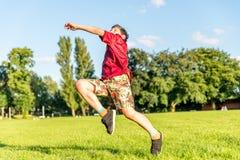 Futbolista joven del muchacho en el estadio que golpea la bola con el pie Imagen de archivo libre de regalías