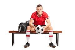 Futbolista joven que se sienta en un banco Fotografía de archivo