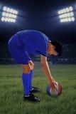 Futbolista listo para golpear una bola con el pie Imagen de archivo libre de regalías