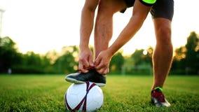 Futbolista profesional en la práctica que ata cordones en las botas Primer con la bola almacen de video