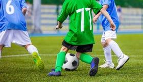 Futbolista que corre con la bola en la echada Imágenes de archivo libres de regalías