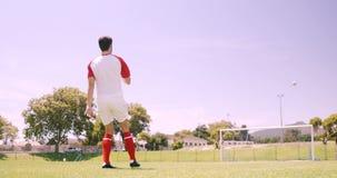 Futbolista que golpea la bola con el pie almacen de video