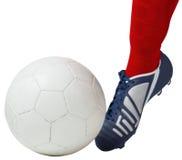 Futbolista que golpea la bola con el pie con la bota Fotografía de archivo libre de regalías