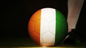 Futbolista que golpea la bola de la bandera con el pie de Costa de Marfil libre illustration