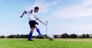 Futbolista que golpea una bola con el pie en el campo almacen de metraje de vídeo