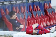 Futbolista que se sienta en el banco Imagenes de archivo