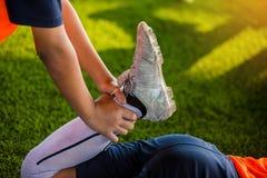 Futbolista trzyma kostkę rozciągać mięśnie zdjęcia stock
