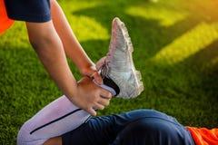 Futbolista trzyma kostkę rozciągać mięśnie zdjęcia royalty free