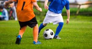 Futbolistas del fútbol de los niños Futbolistas que golpean el juego del partido con el pie de fútbol en la hierba Foto de archivo