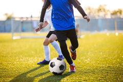 Futbolistas del fútbol que corren con la bola Futbolistas que golpean la bola del fútbol con el pie Fotos de archivo