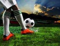 Futbolistas del fútbol que golpean con el pie al balón de fútbol Imagen de archivo libre de regalías