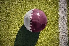 Futbolowa piłka z flaga państowowa Qatar kłama na polu Zdjęcia Royalty Free