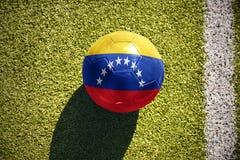 Futbolowa piłka z flaga państowowa Venezuela kłama na polu Fotografia Stock