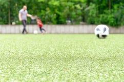 Futbolowy gazon, ojciec i dzieciak bawić się w plecy, obraz stock