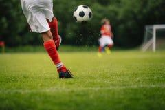 Futbolowy kopni?cie Młodość gracza kopania piłki nożnej piłka na polu obraz royalty free