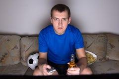 Futbolowy zwolennik w jednolitym ogląda tv Zdjęcia Stock