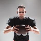 Futbolu amerykańskiego gracz pozuje z piłką na białym tle Zdjęcie Royalty Free