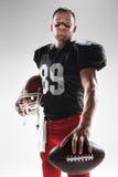Futbolu amerykańskiego gracz pozuje z piłką na białym tle Fotografia Royalty Free