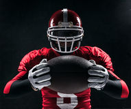 Futbolu amerykańskiego gracz pozuje z piłką na czarnym tle Zdjęcie Stock