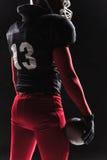 Futbolu amerykańskiego gracz pozuje z piłką na czarnym tle Obrazy Royalty Free