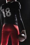 Futbolu amerykańskiego gracz pozuje z piłką na czarnym tle Zdjęcia Stock